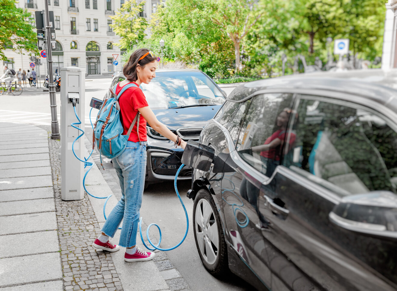 Woman charging her electro car at special parking, alternative energy and eco concept