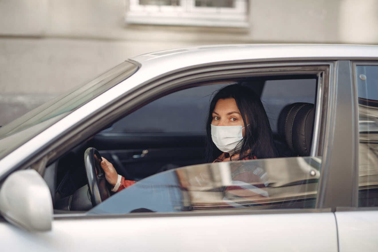 young-woman-wearing-medical-mask-driving-car-3983417